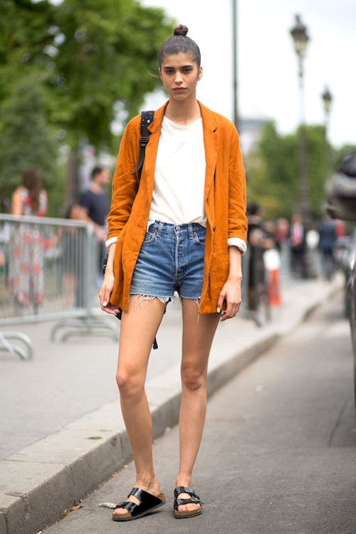 Le-Fashion-Blog-Model-Off-Duty-Style-Top-Knot-Orange-Blazer-White-Tee-Cut-Off-Denim-Shorts-Black-Birkenstock-Sandals-Via-Harpers-Bazaar