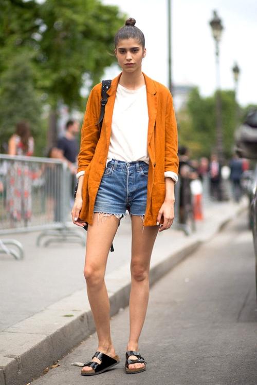 Le-Fashion-Blog-Model-Off-Duty-Style-Top-Knot-Orange-Blazer-White-Tee-Cut-Off-Denim-Shorts-Black-Birkenstock-Sandals-Via-Harpers-Bazaar